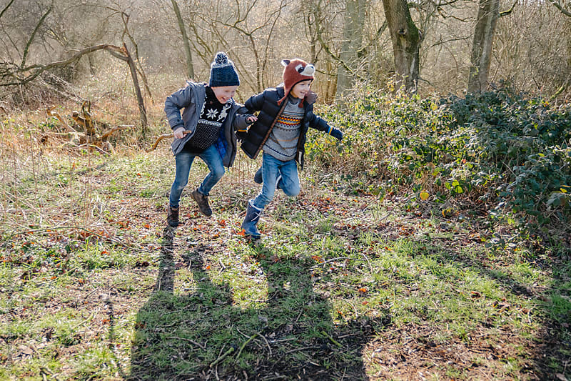 Laughing best friends running through the woods by Rebecca Spencer for Stocksy United