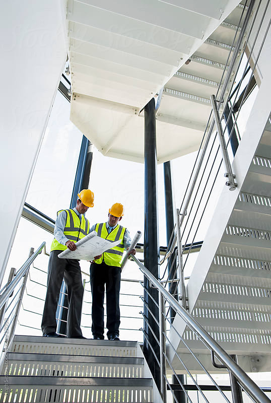 Two Surveyors looking at plans in office building stairway.  by Hugh Sitton for Stocksy United
