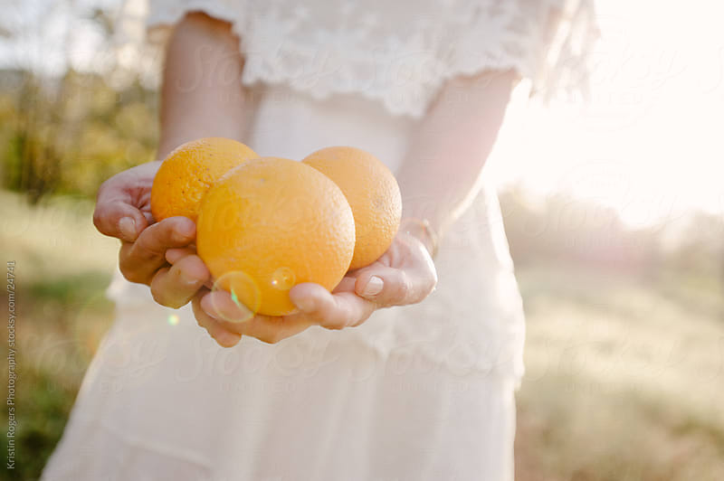 Woman holding oranges in a field by Kristin Rogers Photography for Stocksy United
