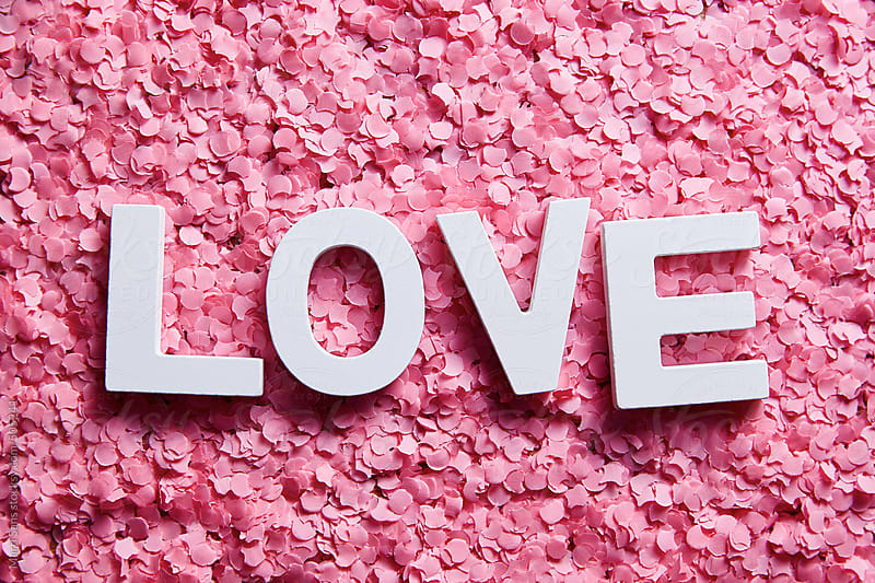 Love word written on pink confetti by Martí Sans for Stocksy United