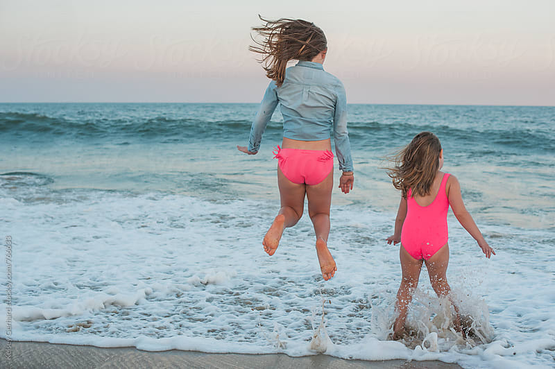 Two girls jump in the sea at sunset by Kelsey Gerhard for Stocksy United