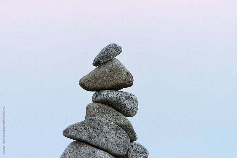 Stack of stones on the beach at sunset by Luca Pierro for Stocksy United