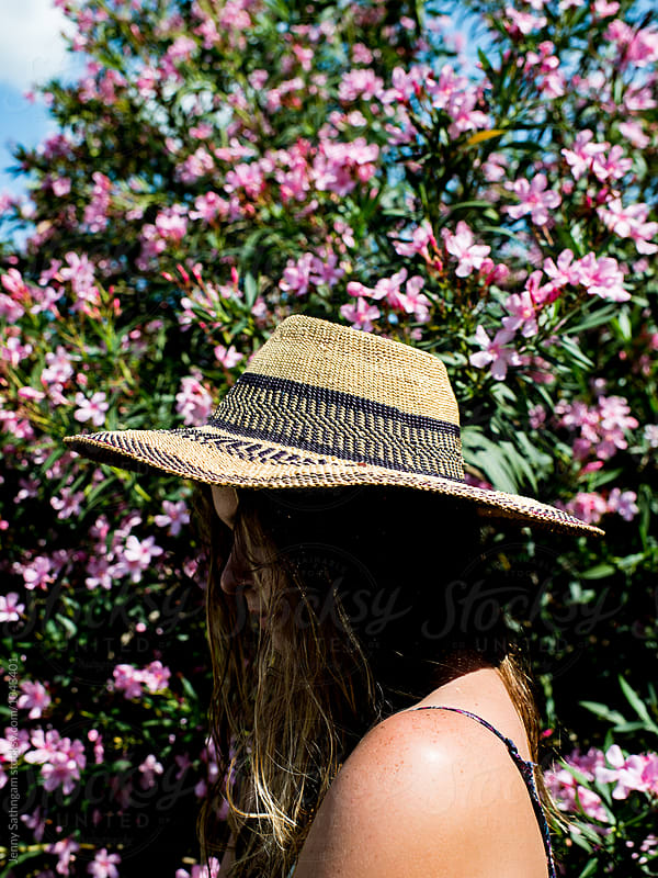 Woman's profile with sunhat and strong shadow in front of pink flower bush by Jenny Sathngam for Stocksy United