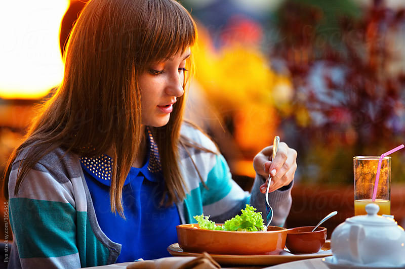 Young woman eating in cafe by Ilya for Stocksy United
