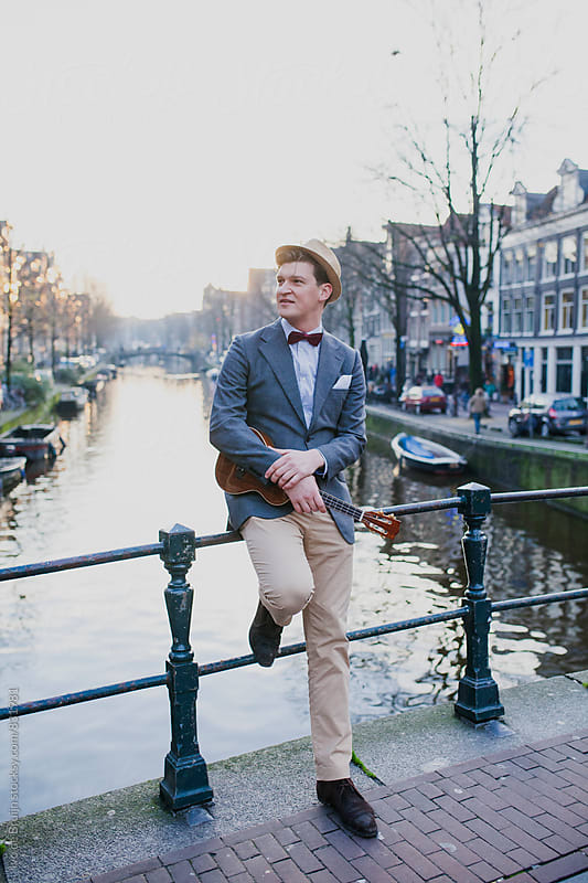 Young man with ukelele standing on a bridge dressed in a classic suit by Ivo de Bruijn for Stocksy United