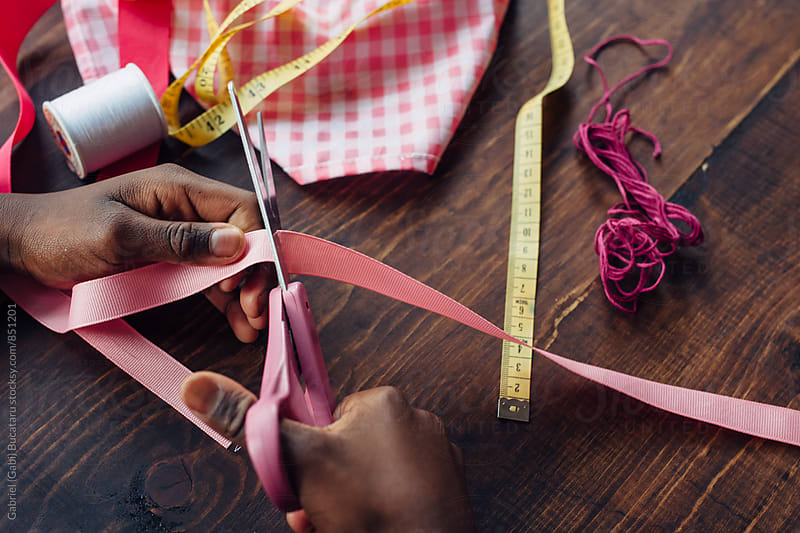 Black girl cutting pink ribbon for a craft by Gabriel (Gabi) Bucataru for Stocksy United