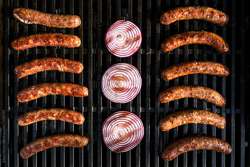 Bratwurst, Kielbasa and red onion on the grill by Adam Nixon for Stocksy United