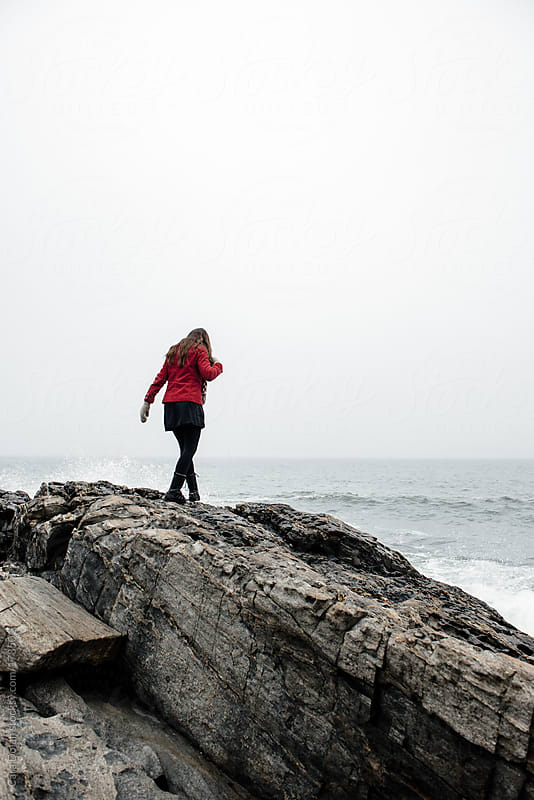 Woman wearing red winter coat stands on a rock overlooking the ocean by Cara Dolan for Stocksy United