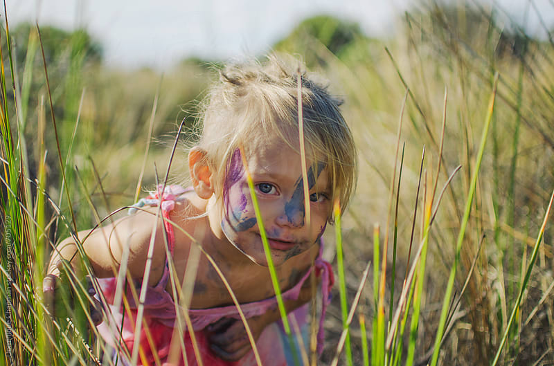 Little girl hiding in long grass by Dominique Chapman for Stocksy United