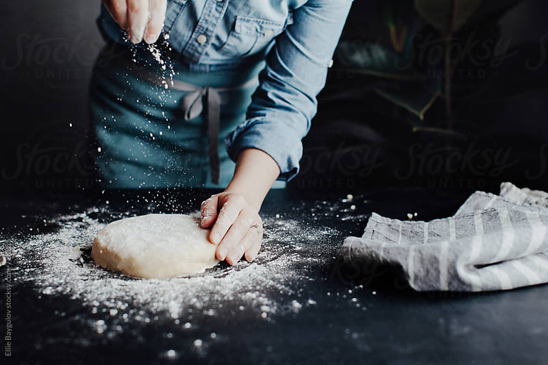 Woman sprinkling flour over dough by Ellie Baygulov for Stocksy United