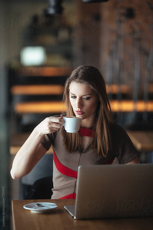 Woman Drinking Coffee and Working on a Laptop by Lumina for Stocksy United