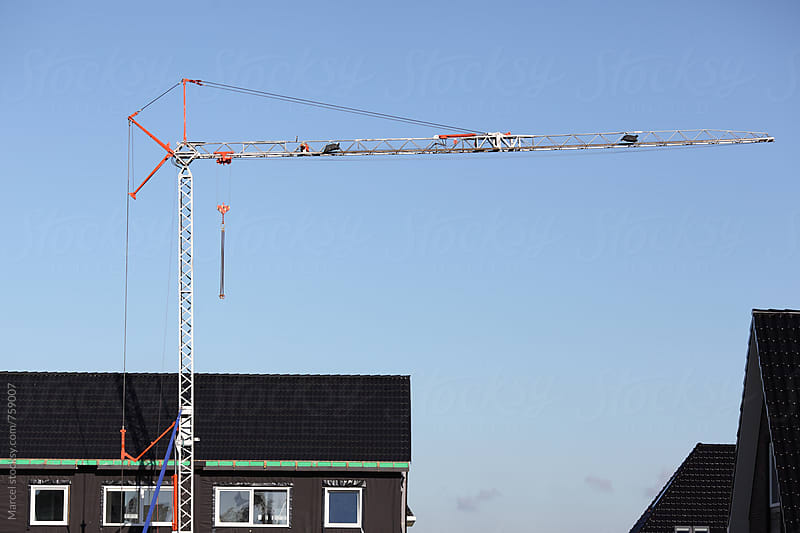 Building new houses with the use of a crane by Marcel for Stocksy United