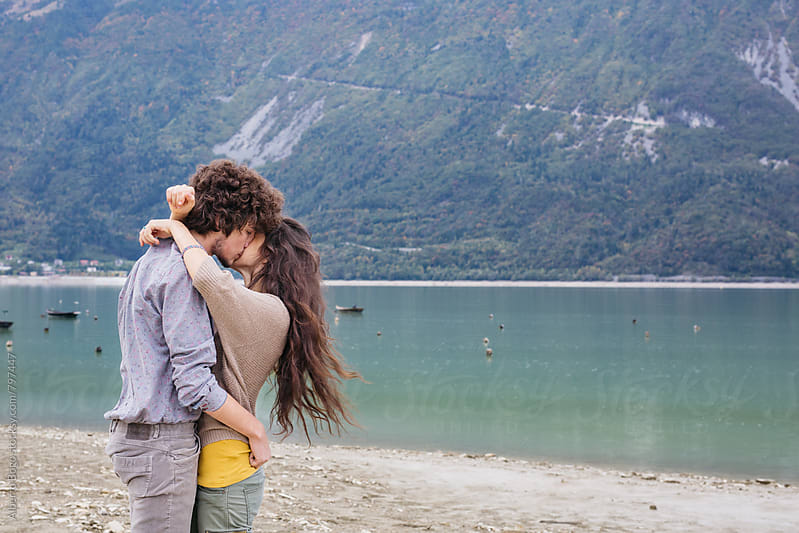 Young couple kissing at the lake by Alberto Bogo for Stocksy United