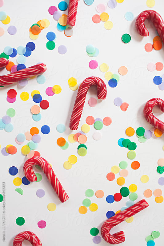 Red and whited striped Christmas candy canes on a white background with confetti by Natalie JEFFCOTT for Stocksy United