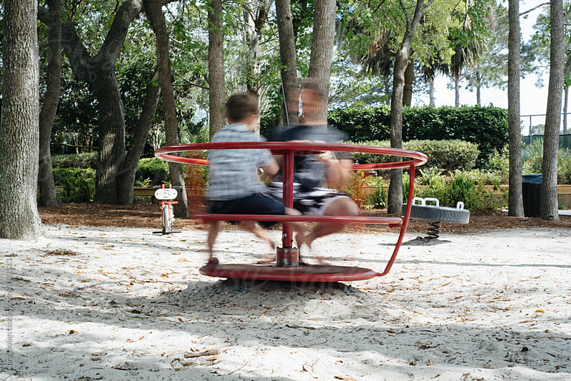 Boy and his dad spin in a merry-go-round on a playground by Cara Dolan for Stocksy United