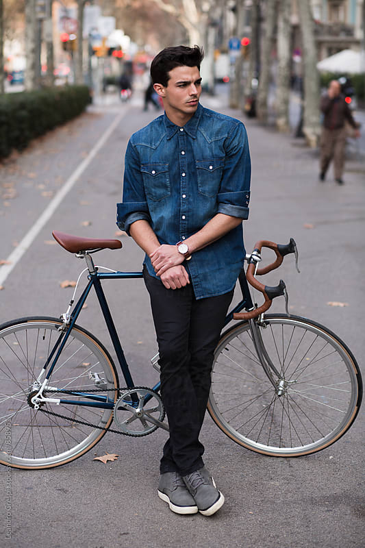 Man in blue shirt outdoors with classic bike by Leandro Crespi for Stocksy United