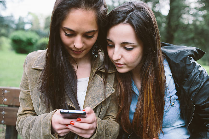 Teenage friends with mobile phone by michela ravasio for Stocksy United