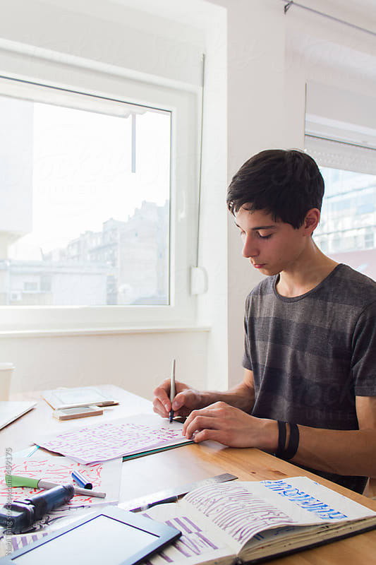 Teenage boy doing homework by the window by Nabi Tang for Stocksy United