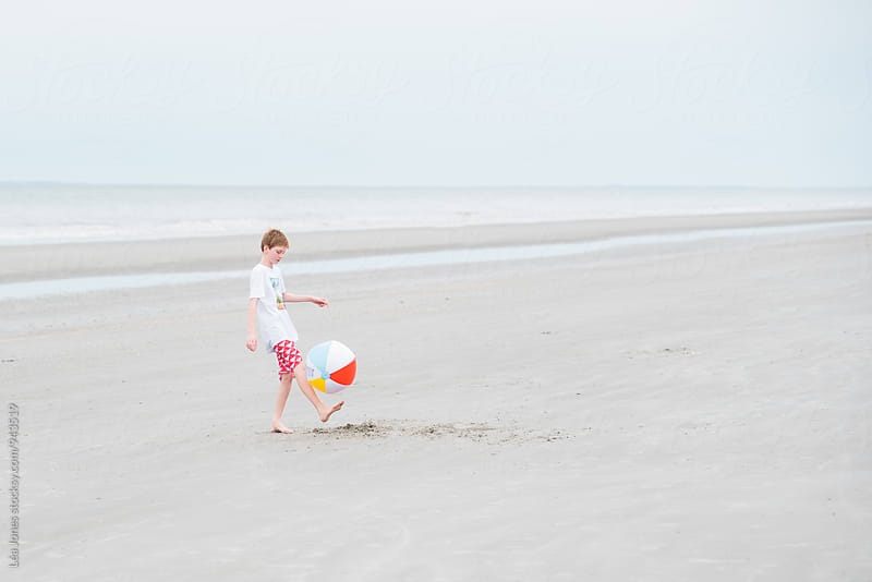 boy playing with ball on the beach  by Léa Jones for Stocksy United