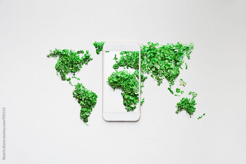 Global green globe concept with a mobile phone by Beatrix Boros for Stocksy United