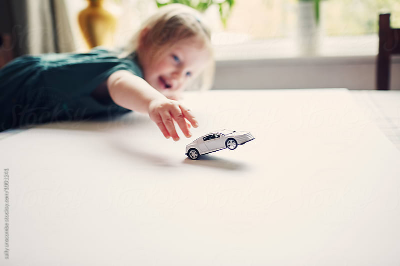 Child playing with a toy car by sally anscombe for Stocksy United