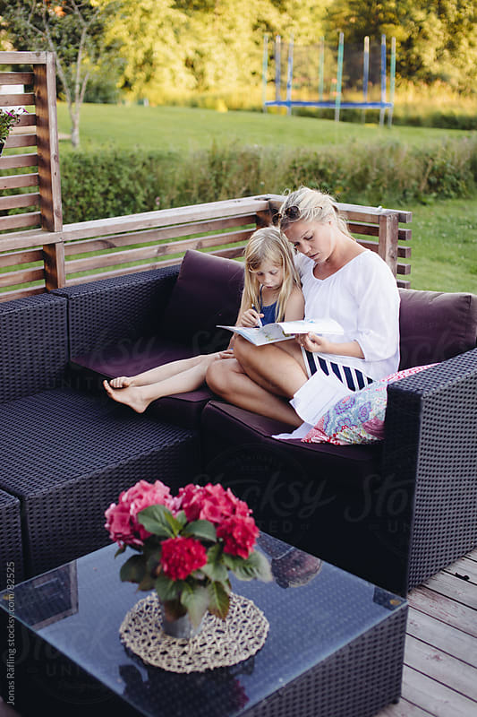 Mother and daughter read a magazine outdoors by Jonas Räfling for Stocksy United