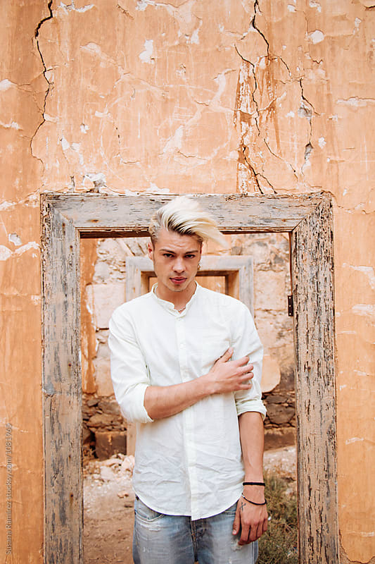 Portrait of young man on a wall with a door frame by Susana Ramírez for Stocksy United