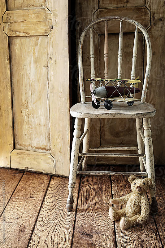 Old chair with toy airplane and teddy bear by Sandra Cunningham for Stocksy United
