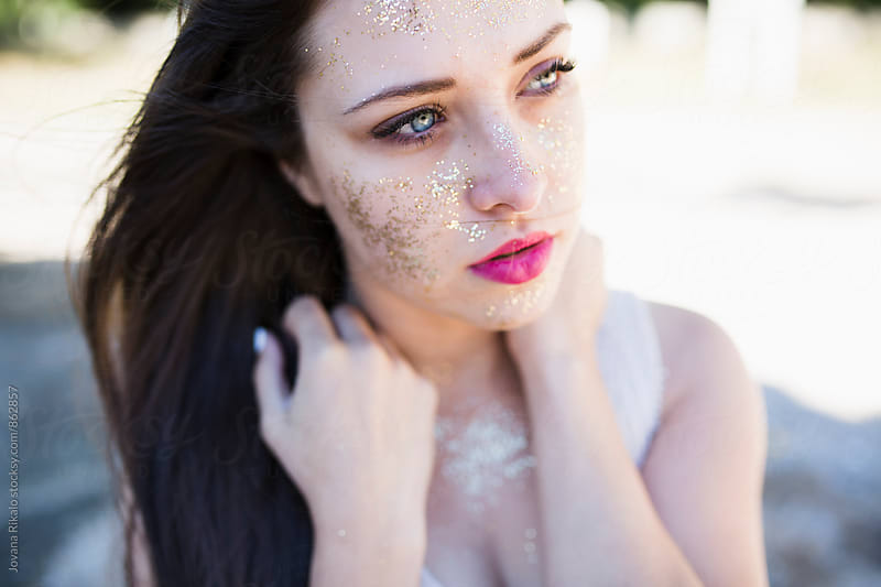 Young woman with glitter all over her face by Jovana Rikalo for Stocksy United