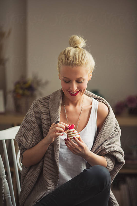 Smiling Woman Holding a Valentine's Day Cookie by Lumina for Stocksy United