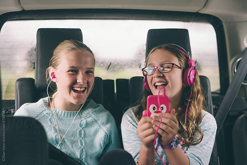 sisters listening to music in the back of the car by Gillian Vann for Stocksy United