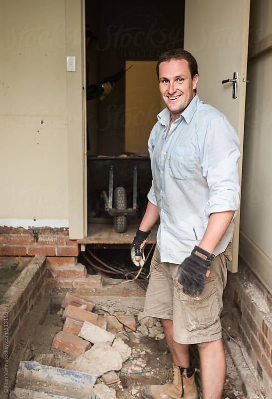 man in the midst of a demolished room by Gillian Vann for Stocksy United