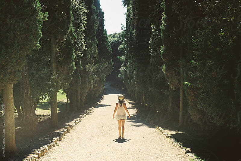 Young girl walking down a path in a Mediterranean forest park by Jovo Jovanovic for Stocksy United