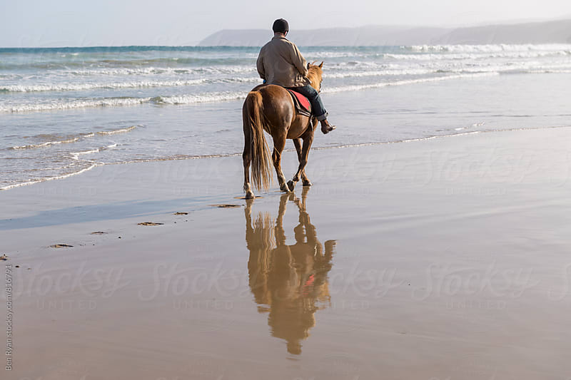 Rear view of senior male riding horseback in shorebreak with reflection on wet sand by Ben Ryan for Stocksy United