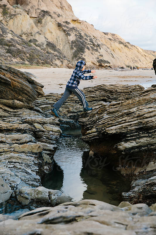 Young boy jumping over a rocky landscape during low tide by Curtis Kim for Stocksy United