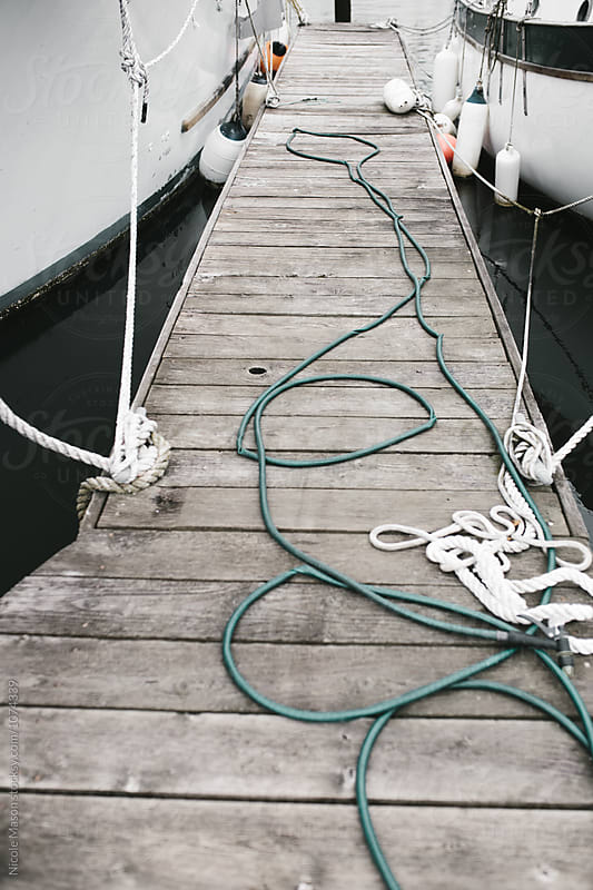 ropes from boats tied to dock by Nicole Mason for Stocksy United