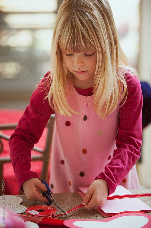 Valentine: Girl Cutting Ribbon For Card by Sean Locke for Stocksy United