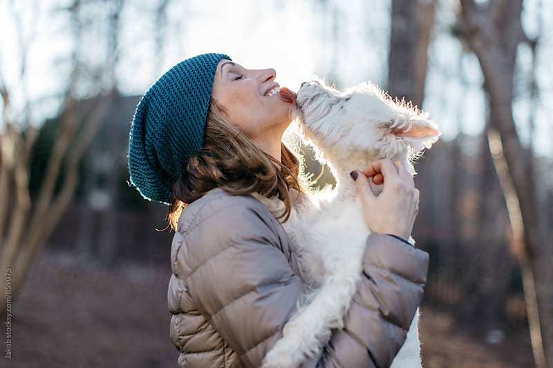 A beautiful woman kissing a small white dog by Jakob for Stocksy United