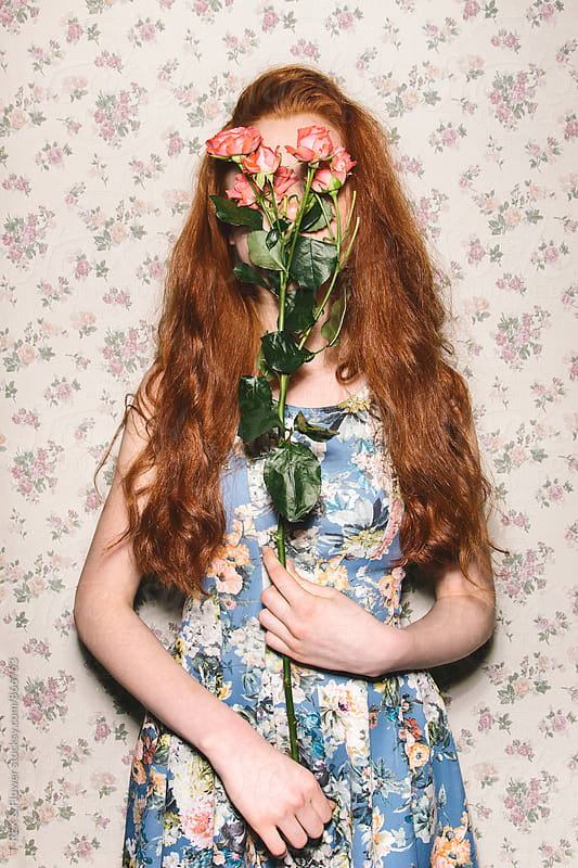 Young red-headed woman covering her face behind pink roses by Danil Nevsky for Stocksy United
