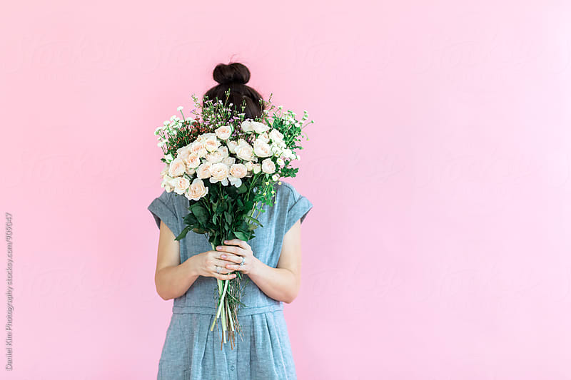 Girl holding flowers in front of colorful wall by Daniel Kim Photography for Stocksy United