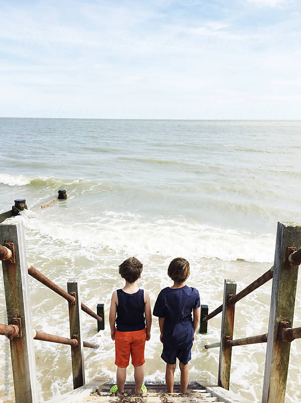 Two boys standing on steps and looking out to sea by Kirstin Mckee for Stocksy United