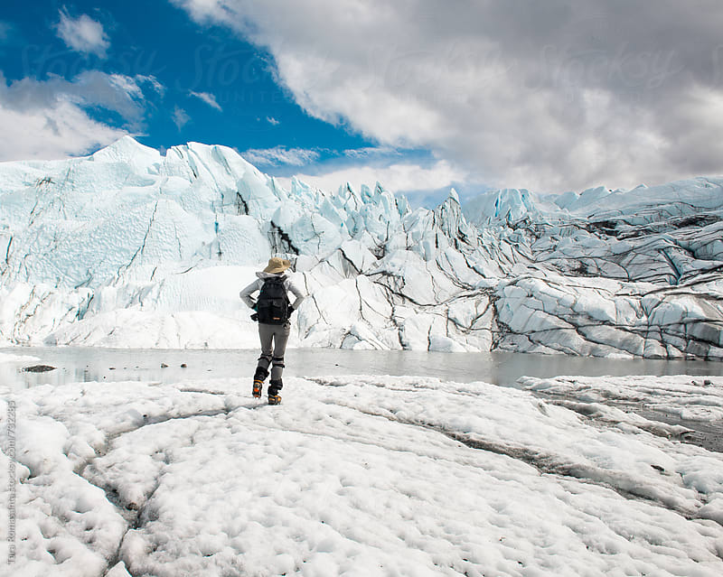 woman trekking toward the face of a glacier by Tara Romasanta for Stocksy United