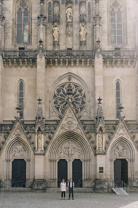 Couple is standing in front of cathedral by Tomas Mikula for Stocksy United