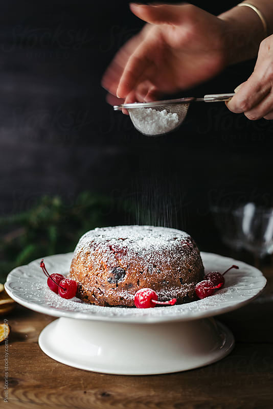 Dusting Christmas pudding with powdered sugar by Pixel Stories for Stocksy United