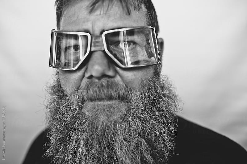 bearded man with vintage bike glasses by Lisa MacIntosh for Stocksy United