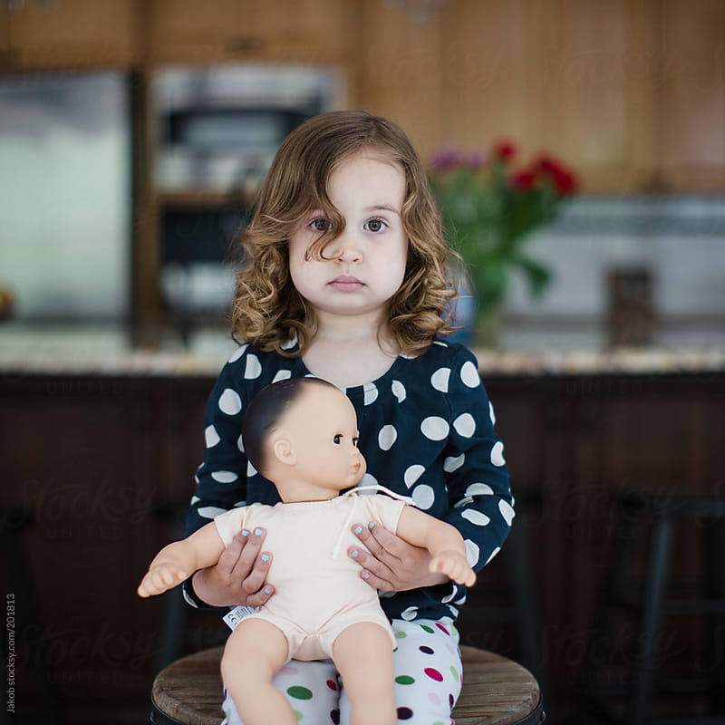 A cute toddler holding a baby doll by Jakob for Stocksy United