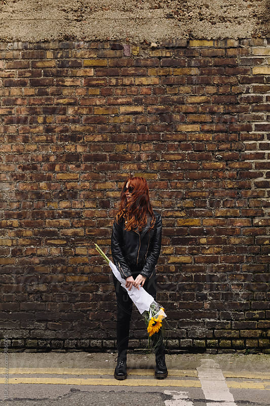 Young Redhead Woman Holding Sunflowers aginst a Wall by HEX. for Stocksy United