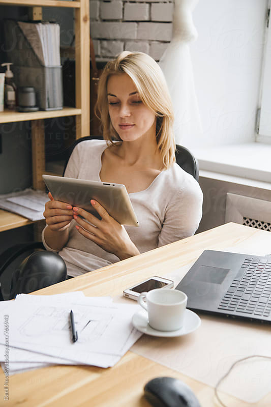 Young blonde woman using a tablet at work by T-REX & Flower for Stocksy United