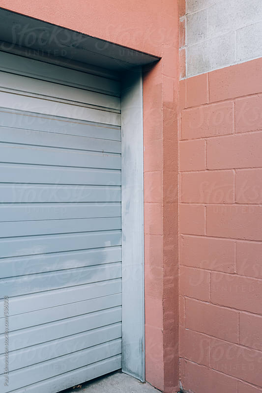 Brightly painted walls and warehouse door, exterior view by Paul Edmondson for Stocksy United