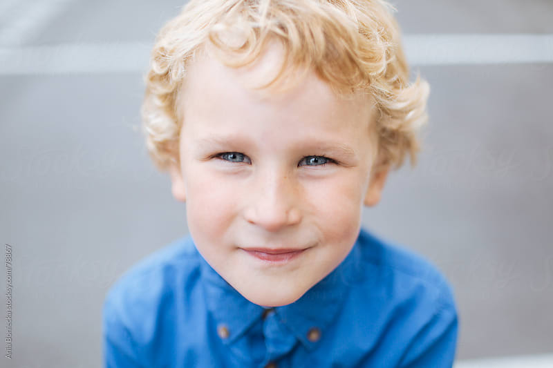 A blonde boy looking up into the camera by Ania Boniecka for Stocksy United